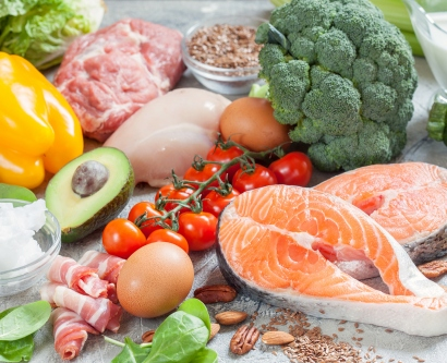 ketogenic diet foods that include avocado, fish, eggs, bacon and broccoli are show on a table