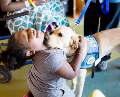 Kimono, a 2-year-old golden retriever/lab, spends time with 9-year-old Jamaira Lampkins