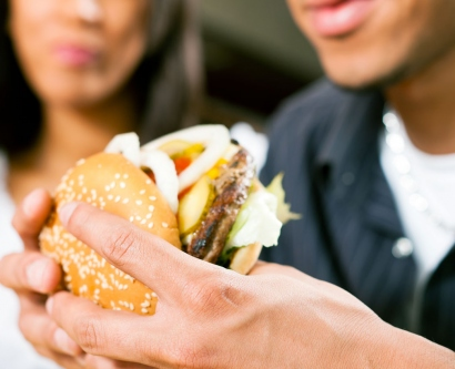 stock image of man eating large hamburger