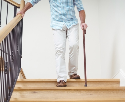 man walking down stairs with a cane