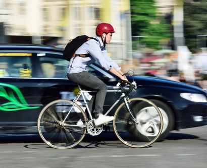 a man rides a bicycle near a car on a street