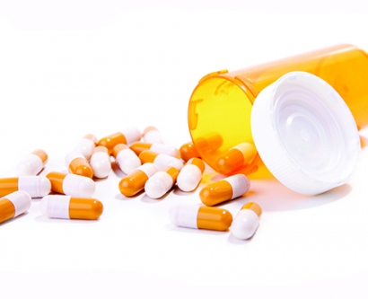 Orange and white pills spilling out of the bottle.