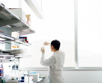 UCSF researcher examines a sample near the window of his lab