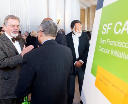 people talking next to an SF CAN sign at a City Hall event