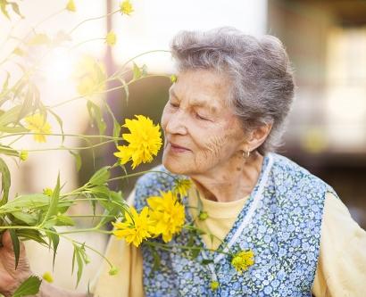 an elderly woman smells a flower