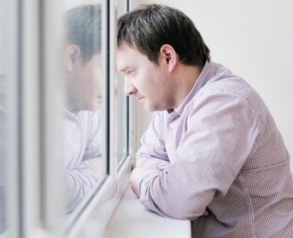 stock image of sad man looking out the window