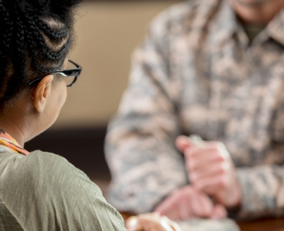 a therapist talks with a person in military clothing