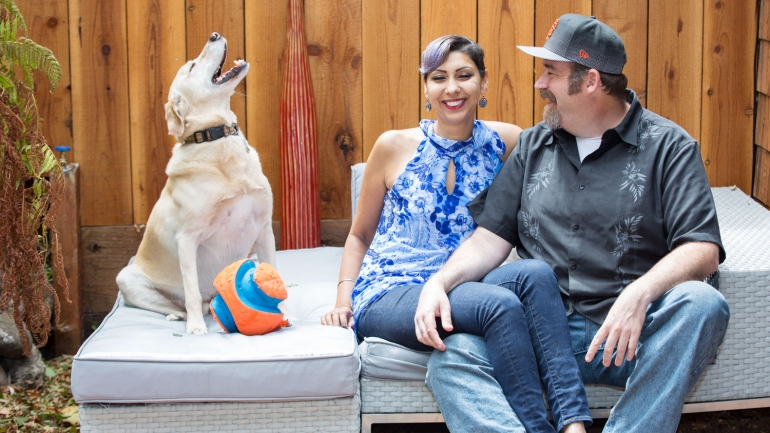 Roopa Grewal laughs while sitting on a sofa with her husband and dog