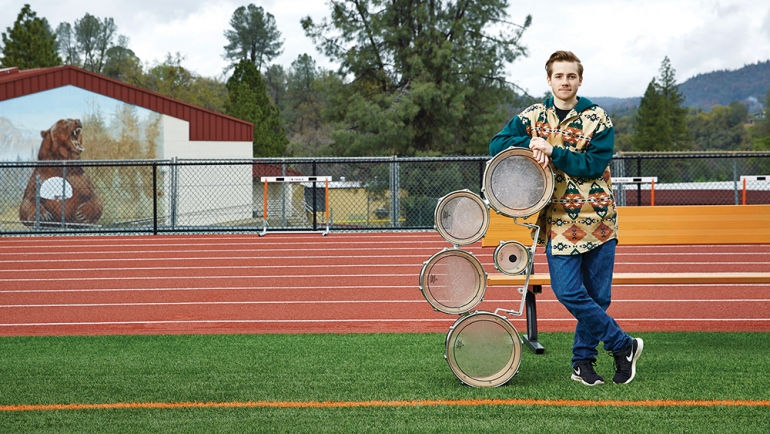 Oliver Bishop leaning on drums in football field