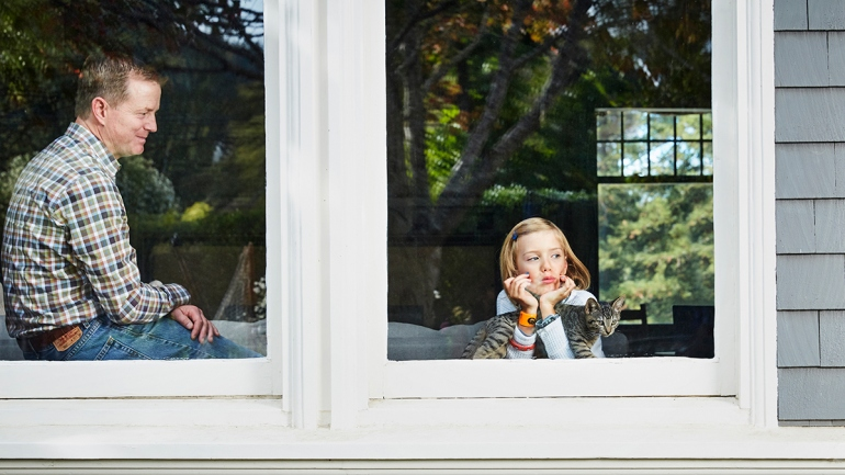 Tim Wood glances lovingly at his daughter as she looks out the window