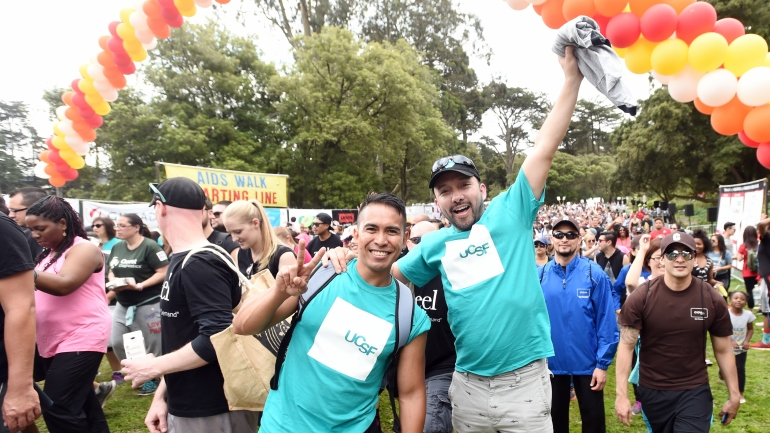 Two UCSF employees wave while participating in AIDS Walk San Francisco 2015