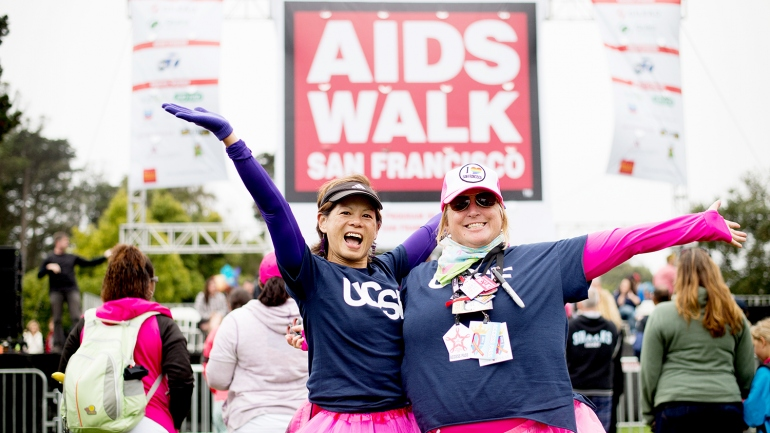 2 women wearing UCSF t-shirts and pink tutus pose in front of the AIDS Walk sign