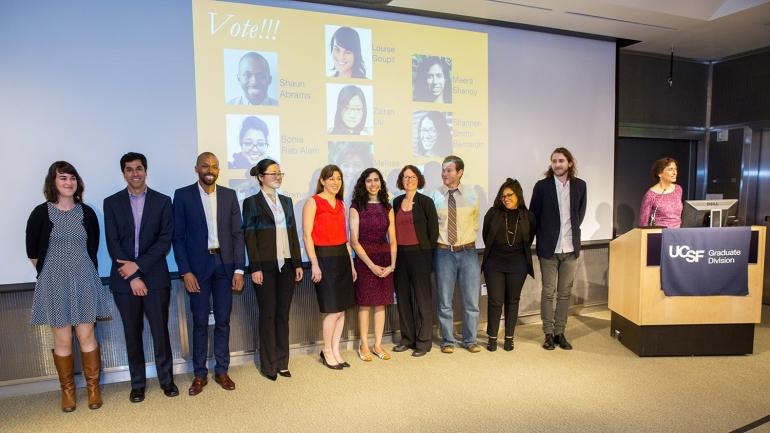 The 10 finalists for the UCSF Grad Slam competition stand before an audience with Graduate Dean and Vice Chancellor for Student Academic Affairs, Elizabeth Watkins