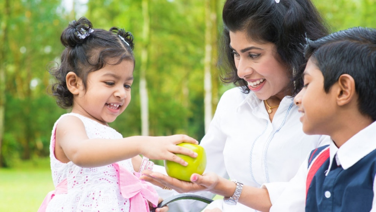 stock image of South Asian child giving an apple to her mother and brother