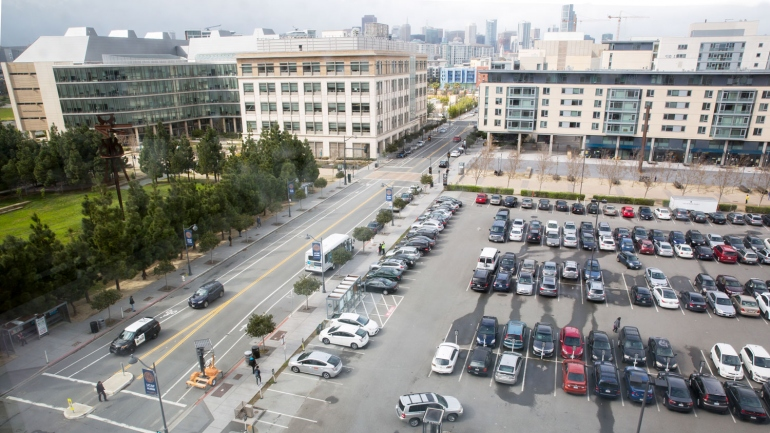 wide view of the Mission Bay campus, with the 4th street surface parking lot in the foreground