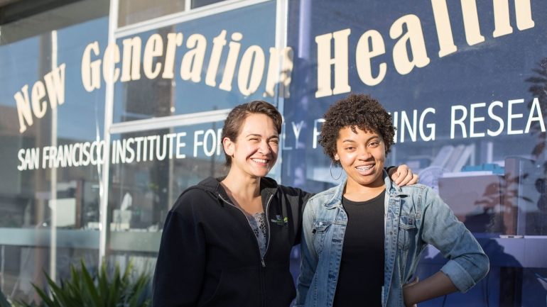 2 women smiling in front of a window that says New Generation Health Center