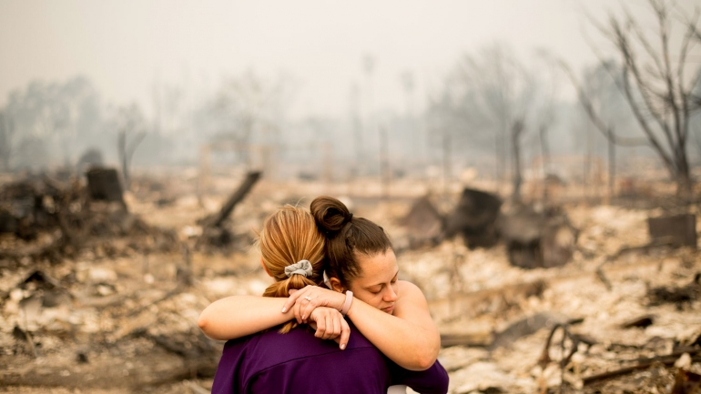 2 women hug in front of a burned out neighborhood