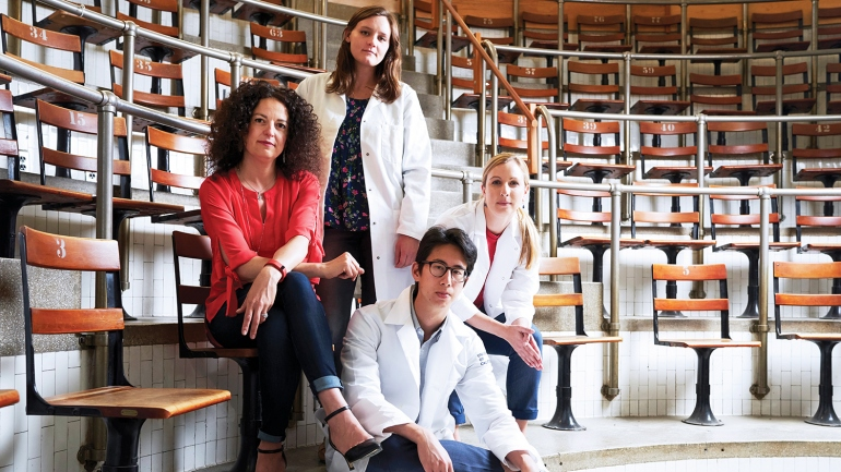 Susanna Rosi sits with three researchers from her lab