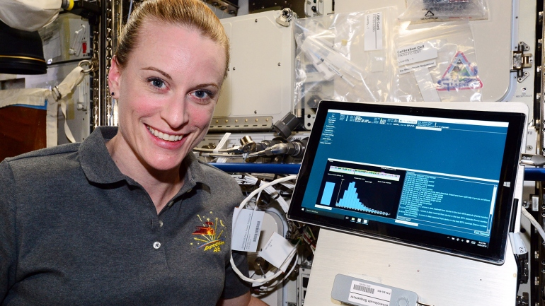 NASA Astronaut Kate Rubins is shown with the MiniON sequencing device aboard the International Space Station.