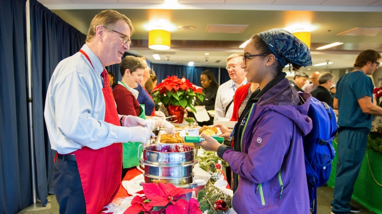 Chancellor Sam Hawgood serves breakfast to staff at Staff Appreciation Holiday Breakfast