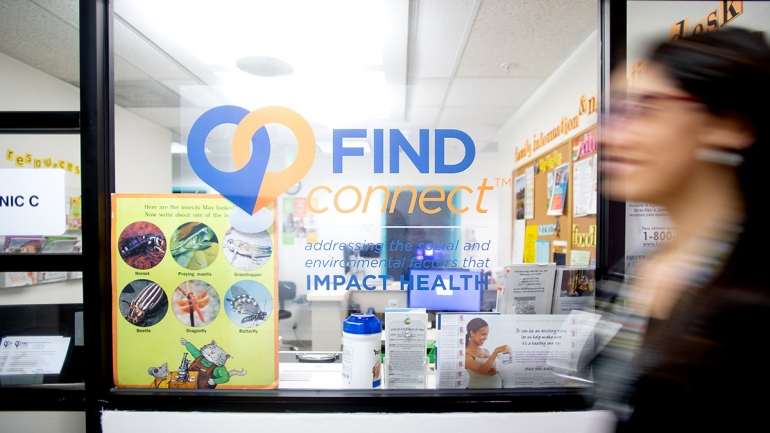a woman walks past a window of the FIND program office