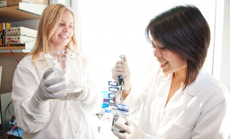 Two researchers work in the lab at the Helen Diller Comprehesive Cancer Center