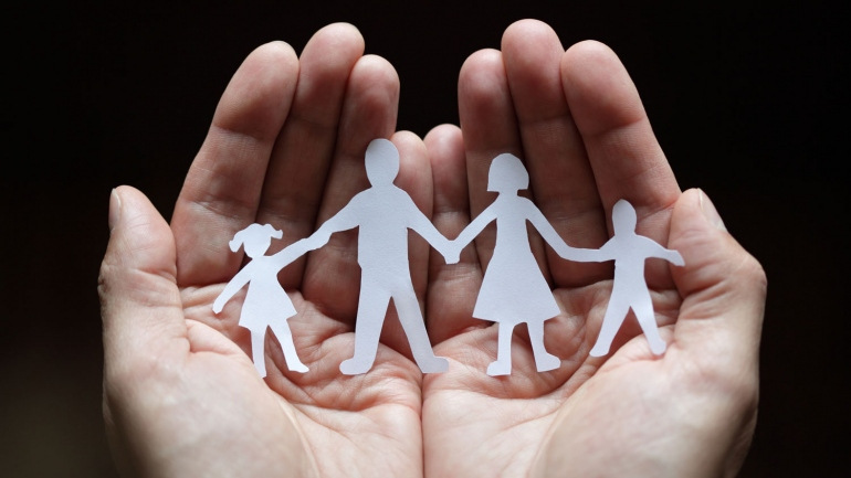 stock image of hands holding a paper cutout of a family