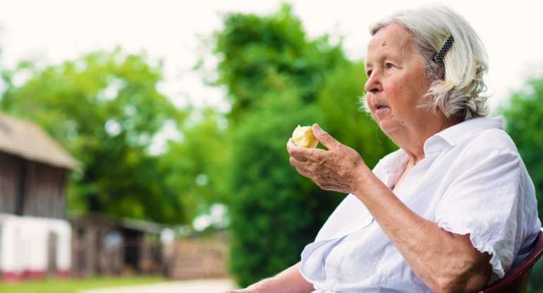 stock image of senior woman eating an apple while sitting outdoors