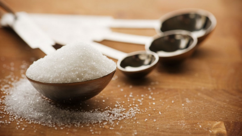 stock image of sugar in measuring spoons