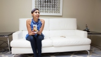 Roopa Grewal sits on her sofa holding a smartphone
