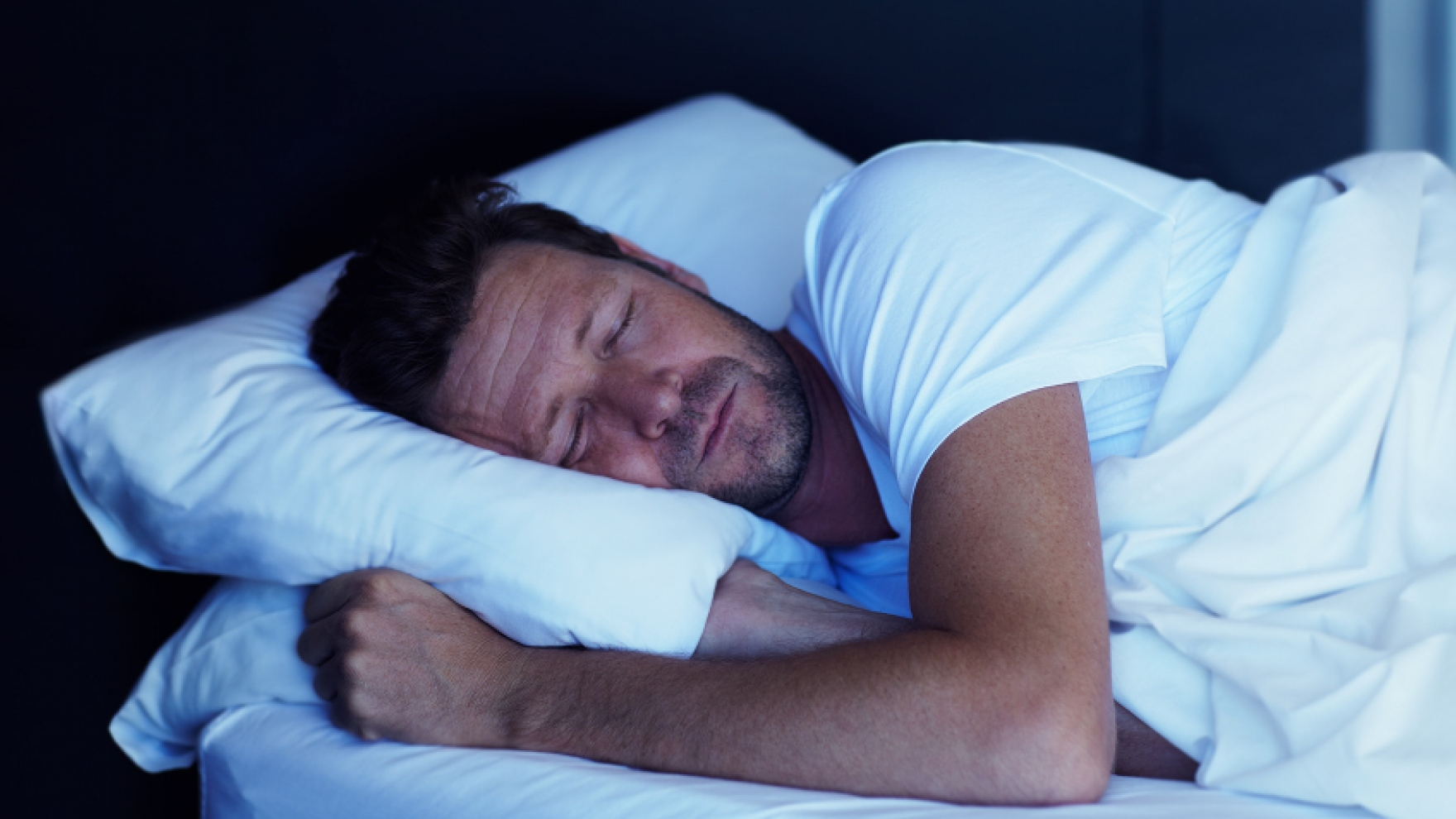 stock image of man sleeping in a bed