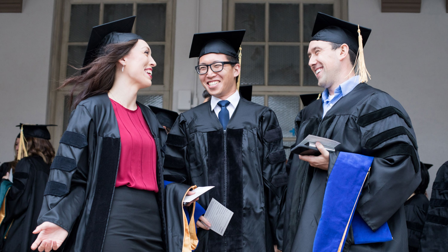 3 UCSF graduates talking in cap and gown