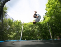 Joshua Osborn does a backflip on the trampoline in the backyard of his home in Cottage G