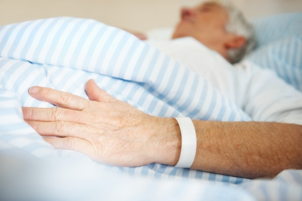 Stock photo of elderly patient in hospital bed