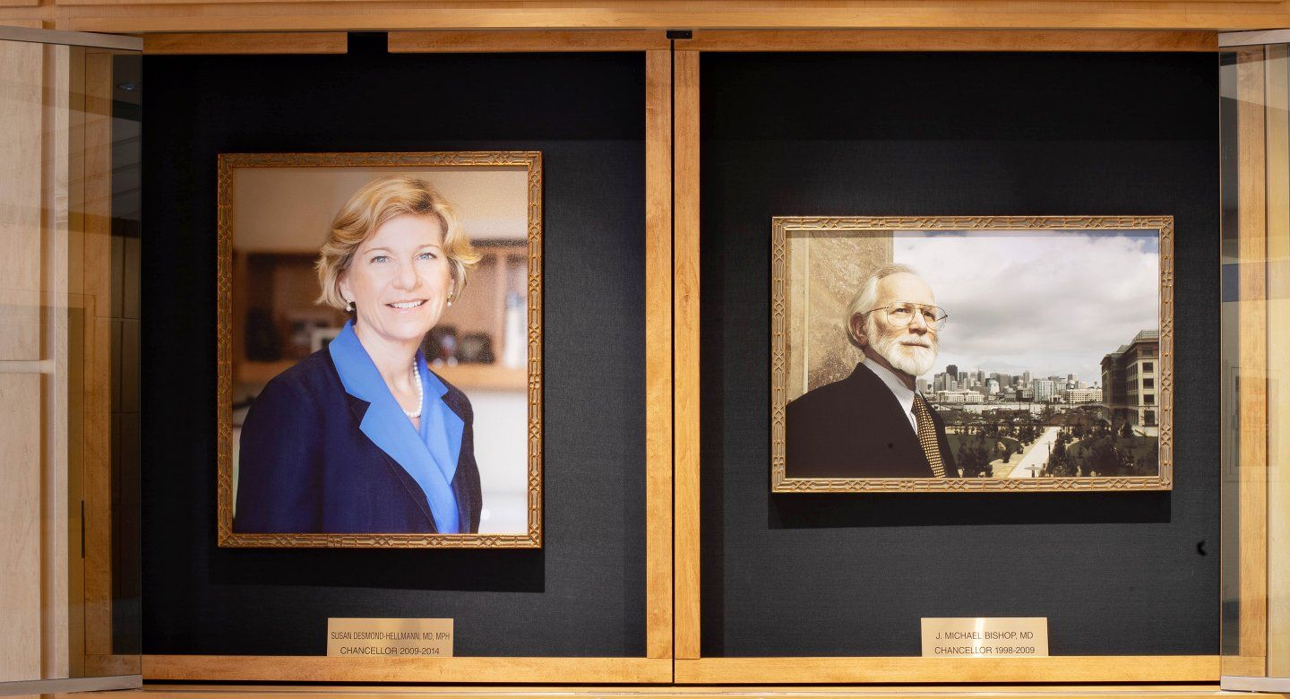 a portrait of Susan Desmond-Hellmann and Michael Bishop hang in the Medical Sciences Building on the Parnassus Heights campus