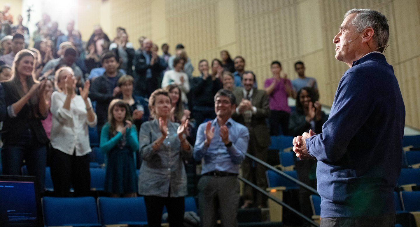 David Wofsy stands in front of a clapping audience at Cole Hall during the Last Lecture event