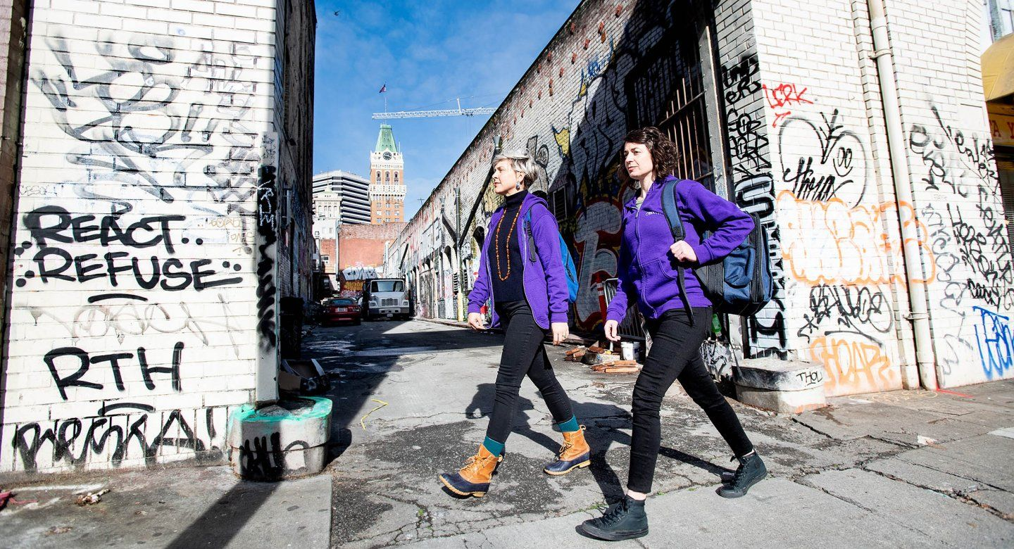 Two public psychiatrists walk by an alley in the streets of Oakland