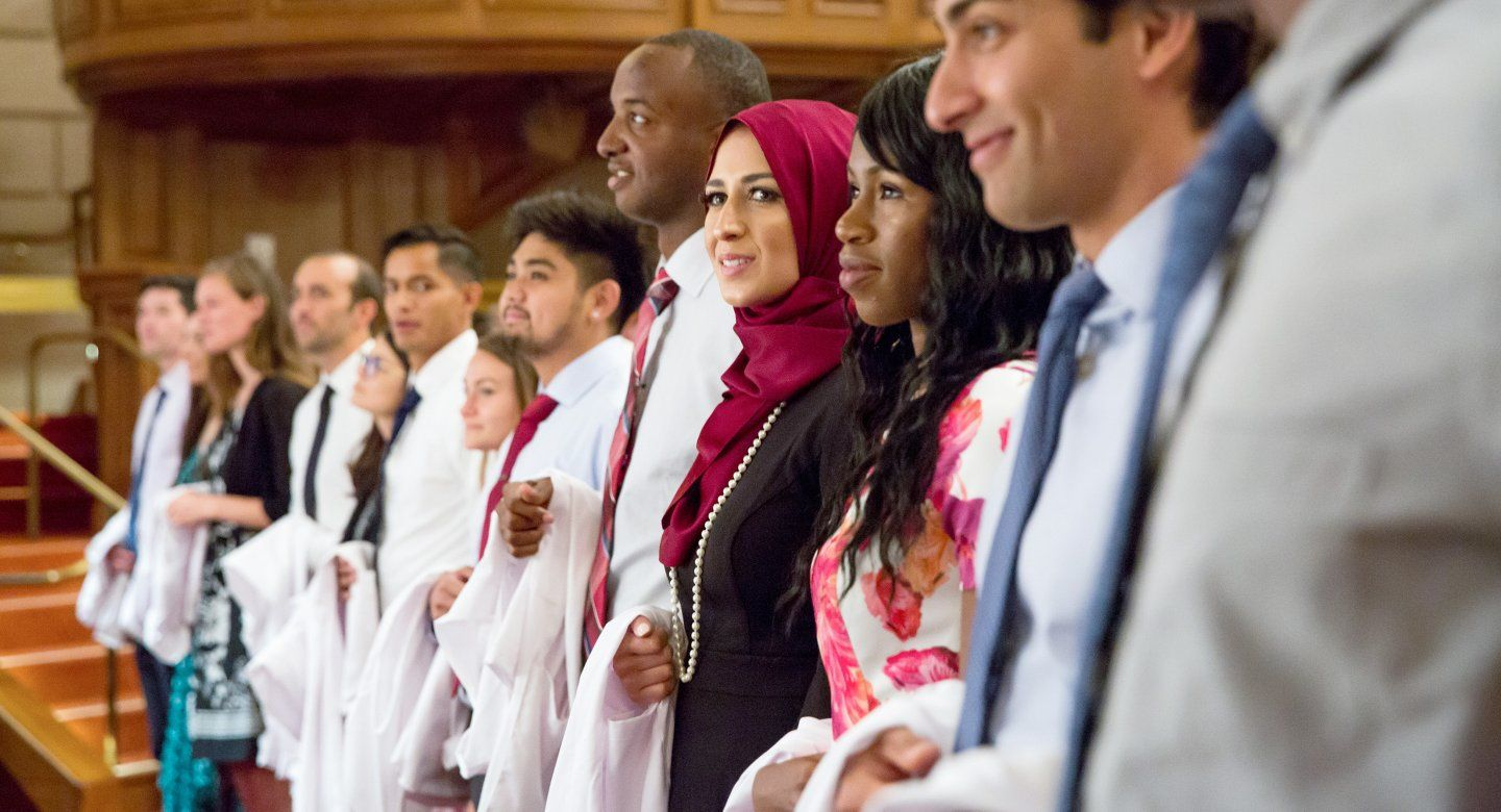 students stand together during white coat ceremony