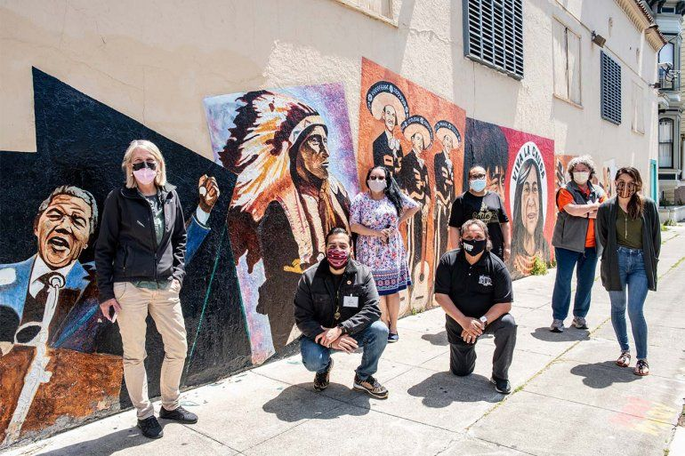 Diane Havlir (far left) and and six members of San Francisco's Latin Task Force gather in front of a mural in the Mission District.
