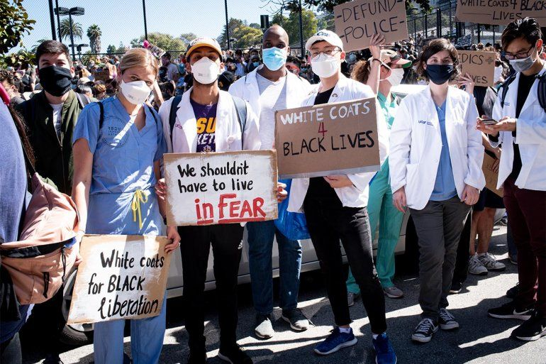 "UCSF students at a protest for the killing of George Floyd. They wear scrubs, white coats, and face masks and hold signs that read ""White coats for Black liberation,"" ""We shouldn't have to live in fear,"" ""White Coast 4 Black Lives,"" and ""Defund Police."""