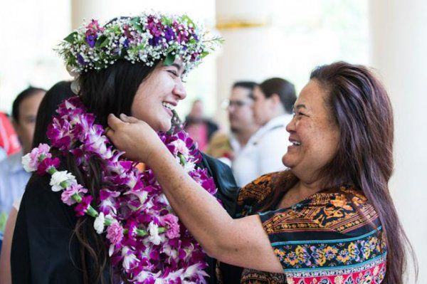 woman gives student a lei