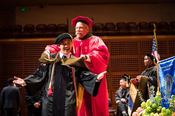Dean Guglielmo hoods Drake Dinh at SOP Commencement 2019