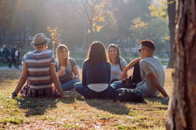 Five young adults sitting in a circle outside