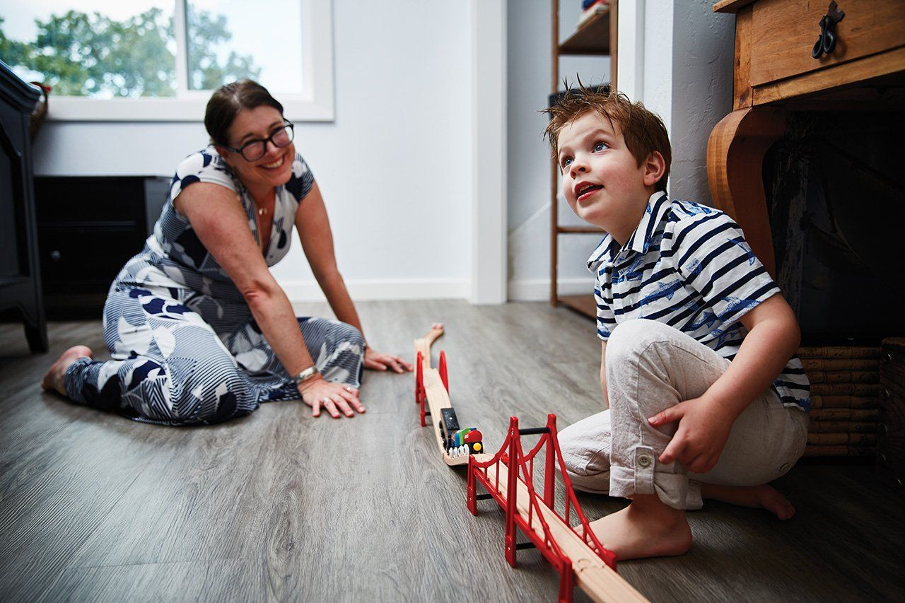 Elysa Marco plays with a train set and her son at their home