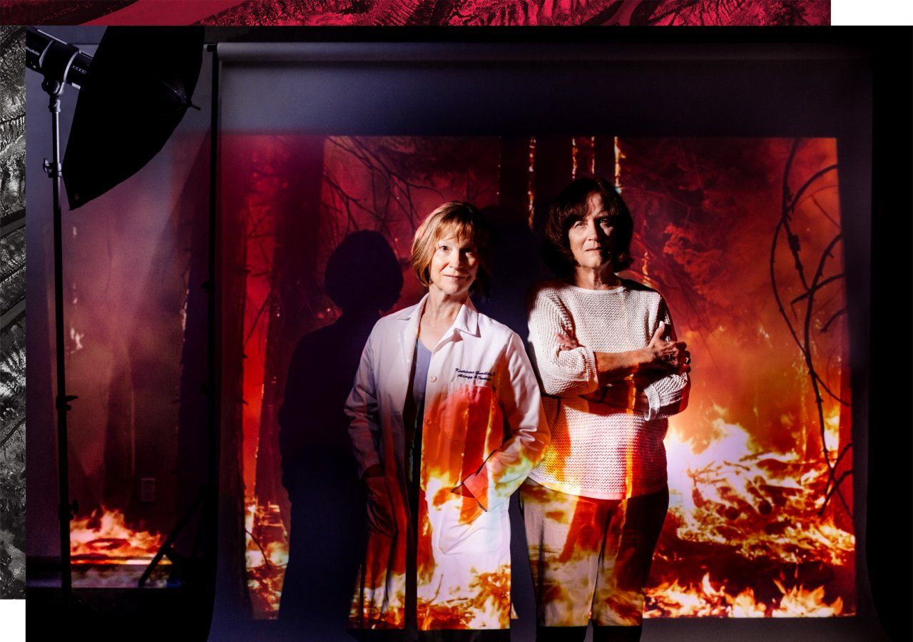 Portrait of Dr. Katherine Gundling and Dr. Wendy Max in a photo studio setting with a projection of a forest fire.
