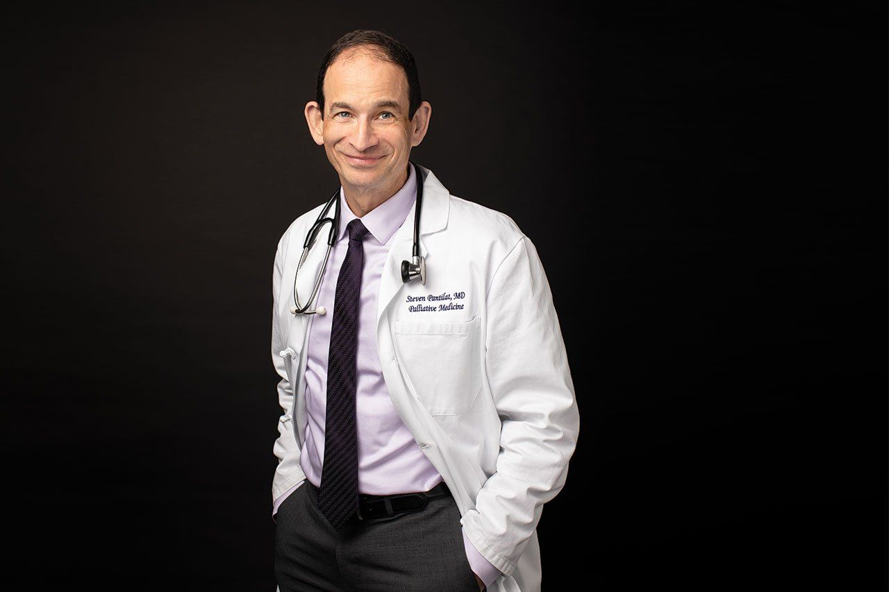 Photo of Steven Pantilat, MD, in a white doctor's coat with a stethoscope draped around his neck, in front a black background.