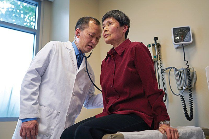 Dr. Nguyen listens to the lungs of a patient