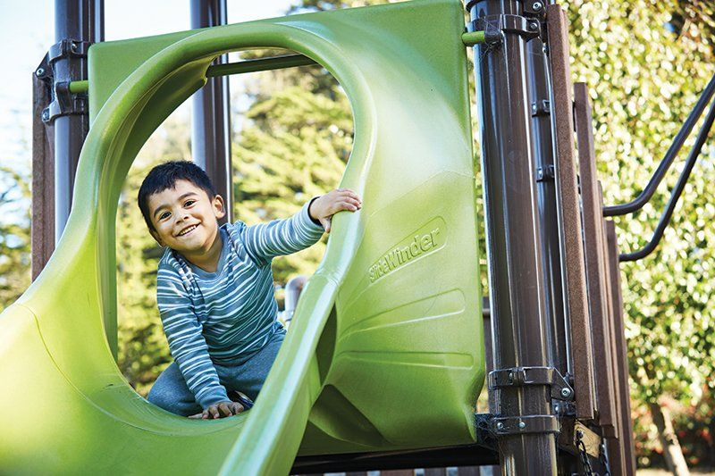 Steven Mendoza smiles at the camera before going down a slide on the playground