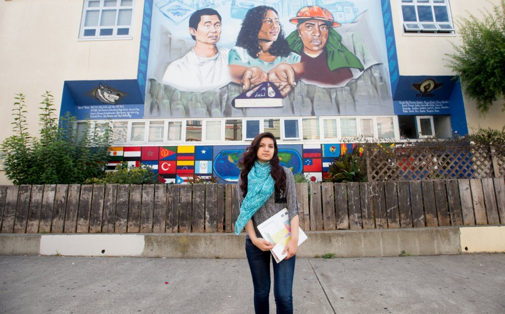 An SEP intern stands in front of a San Francisco high school with a multi-cultural mural