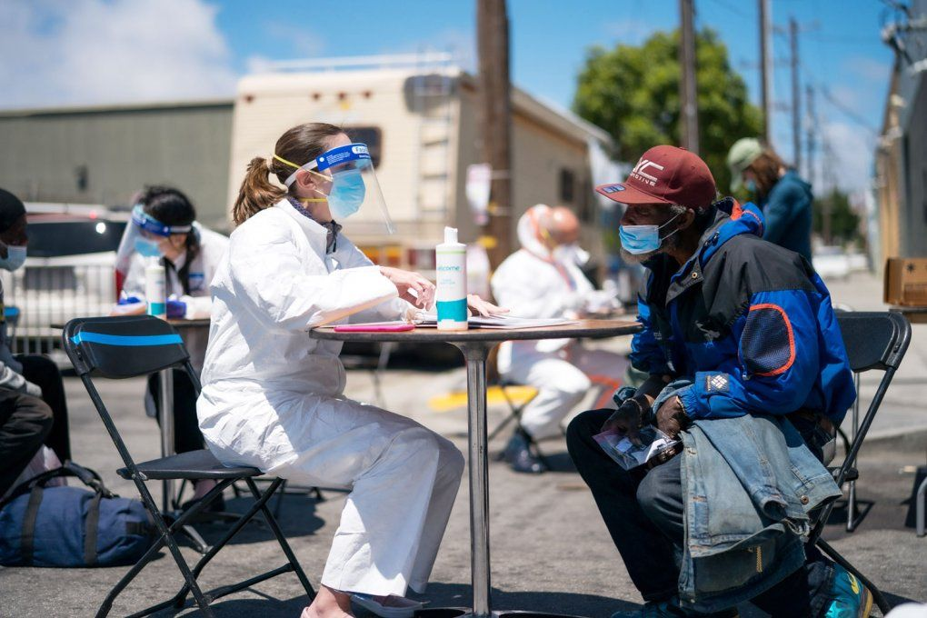 Clinician in PPE talks to unhoused man at an outdoor table